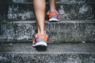 Mężczyzna wchodzący po schodach jako symbol osiągania kolejnych poziomów