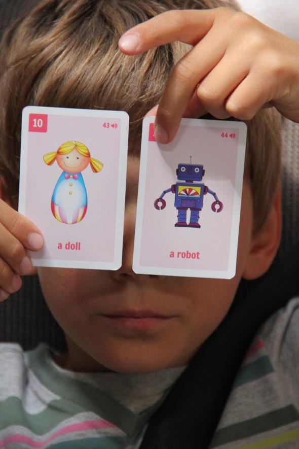 chłopiec trzyma FISZKI obrazkowe do nauki angieslkiego