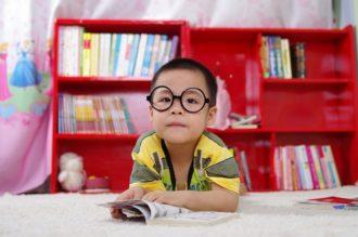 Dziecko na tle regału z książkami