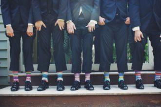 mężczyźni w garniturach i kolorowych skarpetkach