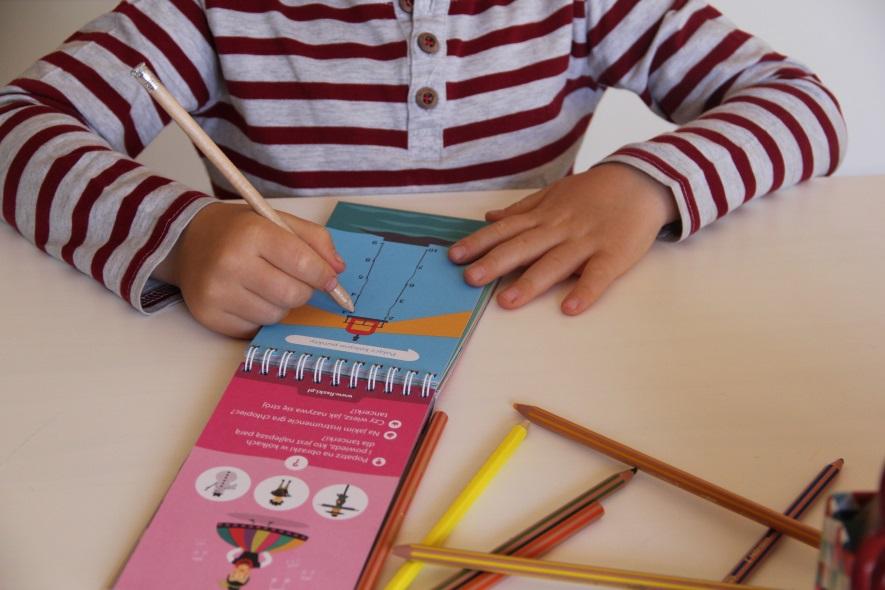dziecko rozwiązuje zadanie połącz kropki